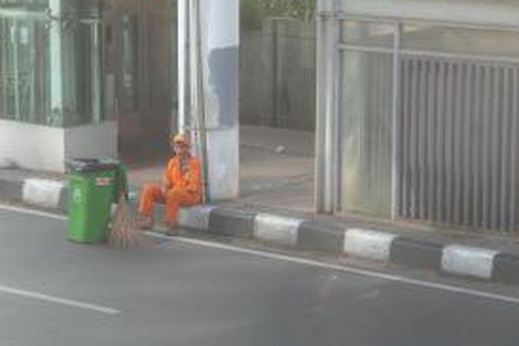 Salah seorang petugas Kebersihan tampak beristirahat sejenak usai menjalankan tugasnya di area car free day di kawasan Bundaran HI, Minggu (28/6/2015)
