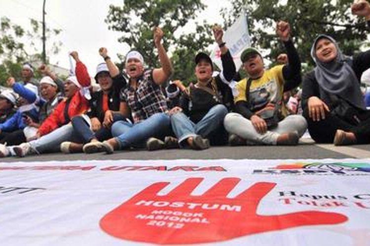 Ilustrasi: para buruh menuntut kenaikan upah dan penghapusan sistem kerja alih daya (outsourcing).