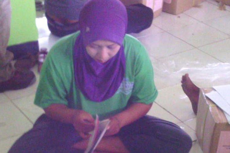 Siti Rohemah, melipat surat suara untuk mencari tambahan penghasilan di luar tugasnya sebagai guru honorer di Pamekasan.