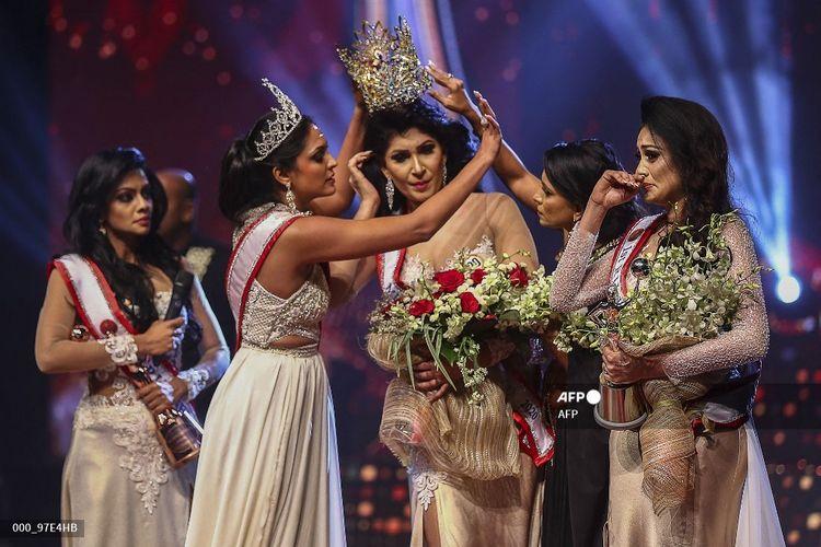 Dalam foto yang diambil pada 4 April 2021, pemenang Mrs World 2020 Caroline Jurie (dua dari kiri) melepaskan mahkota dari juara Mrs Sri Lanka 2021 Pushpika De Silva karena dituduh sudah bercerai.