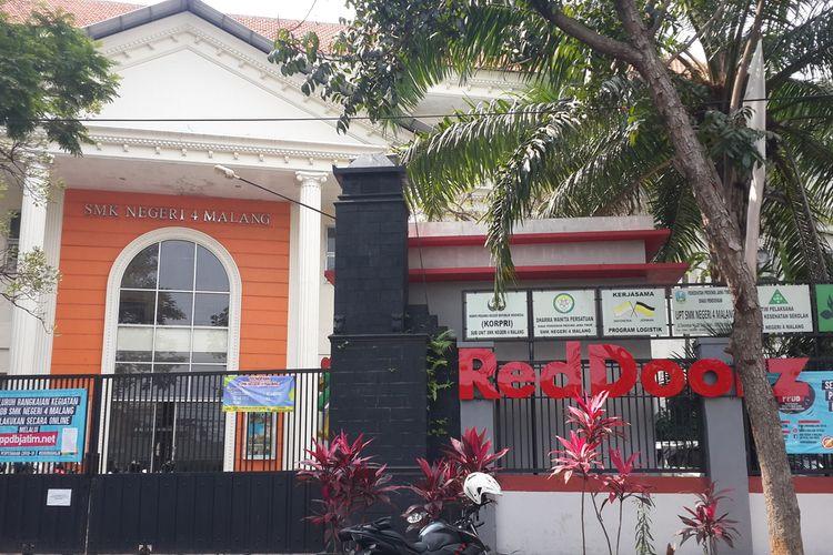 Logo RedDoorz yang terpasangan di depan SMKN 4 Kota Malang, Kamis (16/7/2020)