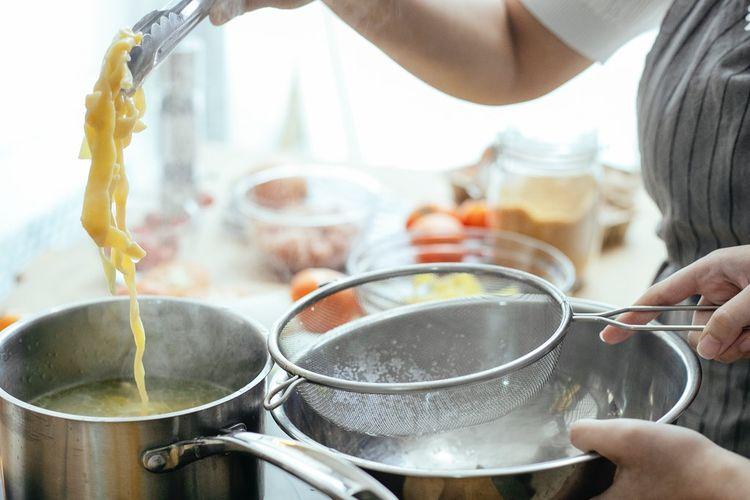 Ilustrasi memasak dengan panci stainless steel.