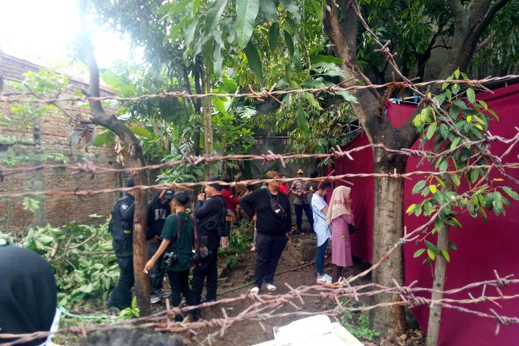 Tampak kerabat dan petugas kepolisian terlihat menunggu pembongkaran makam Lina di luar tenda merah.