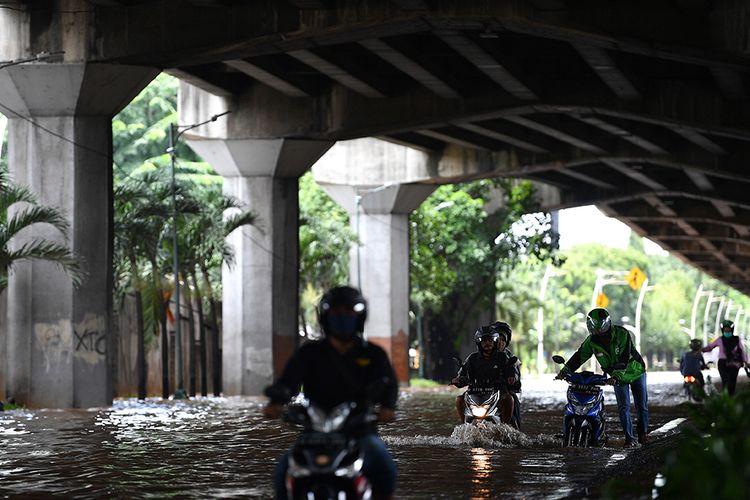 Pengendara sepeda motor mencoba melintasi banjir di Jalan Yos Sudarso, Kelapa Gading, Jakarta Utara, Minggu (23/2/2020). Hujan deras sejak Minggu 23 Februari dini hari membuat sejumlah daerah di Ibu Kota tergenang banjir.