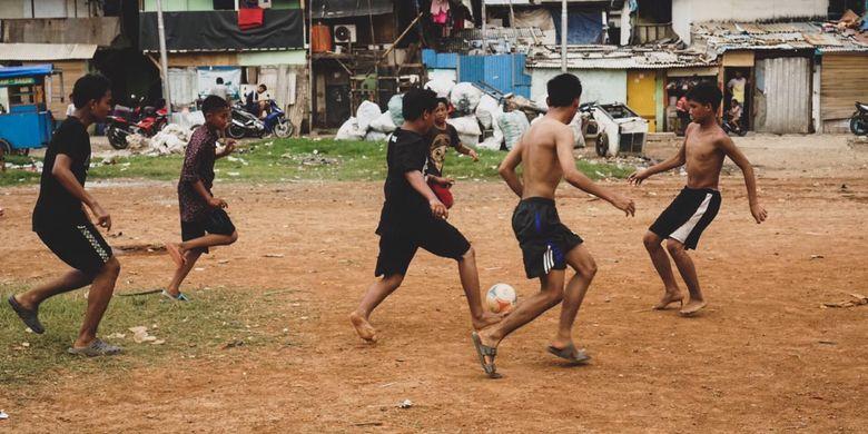 Anak-anak Kampung Muka, Kelurahan Ancol, Kecamatan Pademangan, Jakarta Utara bermain sepak bola di area perkampungan pada Minggu (5/4/2020). Saat ini, Indonesia menghadapi wabah pandemi corona dan mengharuskan setiap orang melakukan pembatasan fisik (physical distancing) untuk mencegah penularan. Pemerintah menyatakan per Senin (6/4/2020) sore, ada 2.491 orang positif corona, 192 orang sembuh, dan 209 orang sembuh.