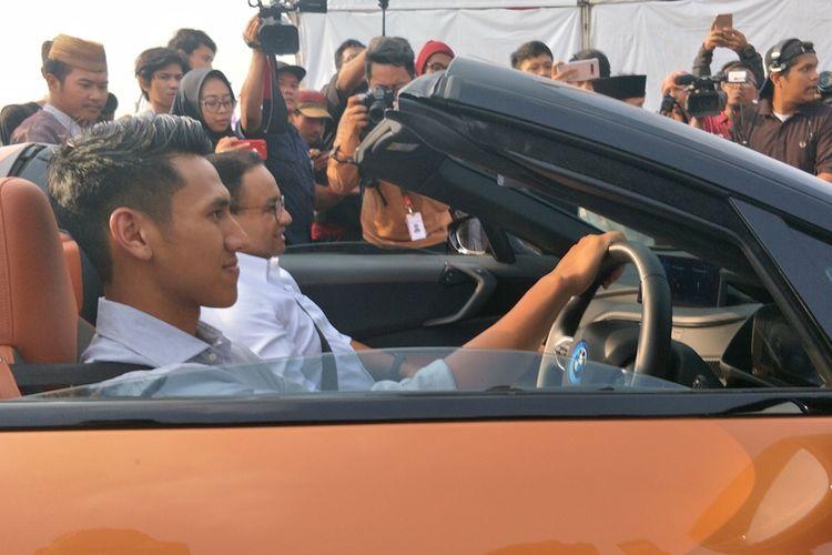 Gubernur DKI Jakarta Anies Baswedan disopiri pembalap Formula 2Sean Gelael saat konvoi mobil listrik dari Kompleks Gelora Bung Karno (GBK) menuju kawasan Monas, Jakarta Pusat, Jumat (20/9/2019) sore.