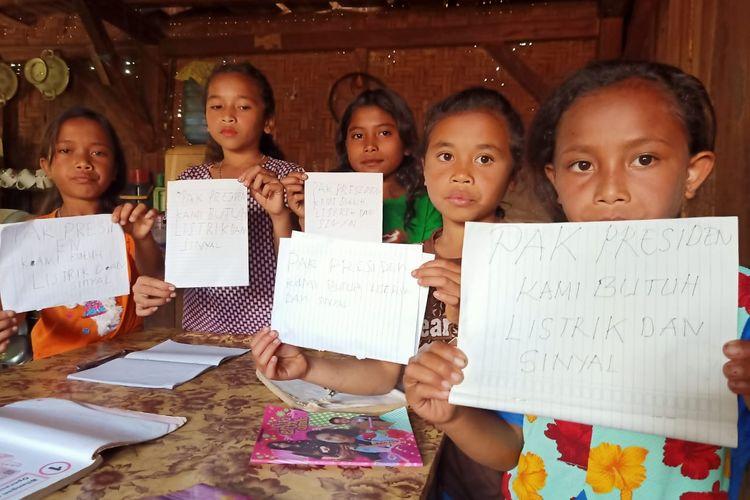 Foto : Beberapa siswi SDI Taga Laga Buru menunjukkan tulisan berisi permintaa kepada Presiden Republik Indonesia, Sabtu (18/7/2020).