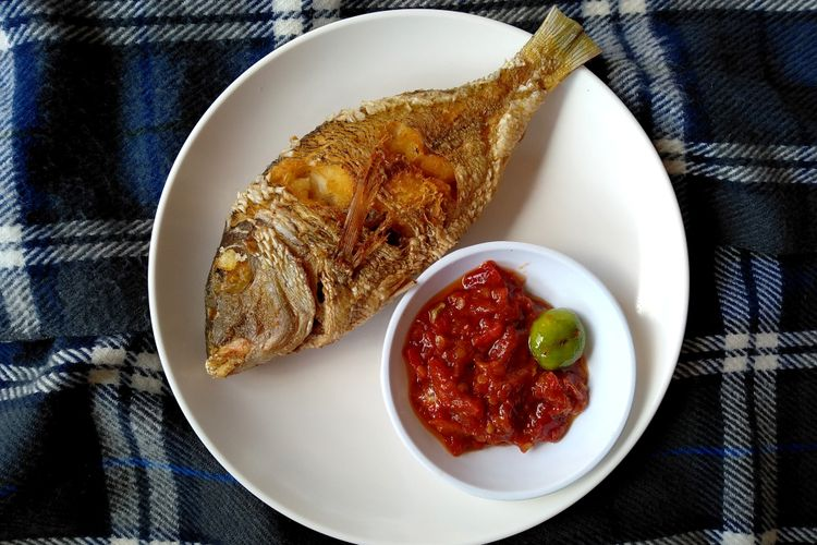 Ilustrasi ikan goreng bumbu kuning.
