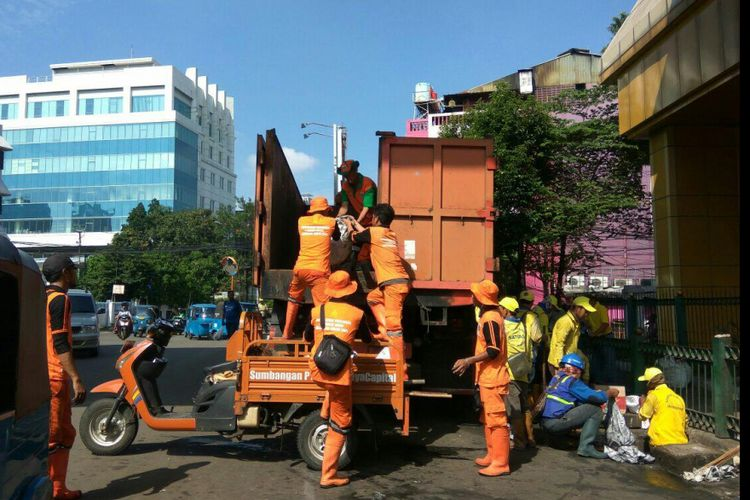 Petugas Prasarana dan Sarana Umum (PPSU) bahu membahu membersihkan sampah dan mengangkutnya ke truk di Jalan Kebon Sirih, Minggu (25/2/2018).