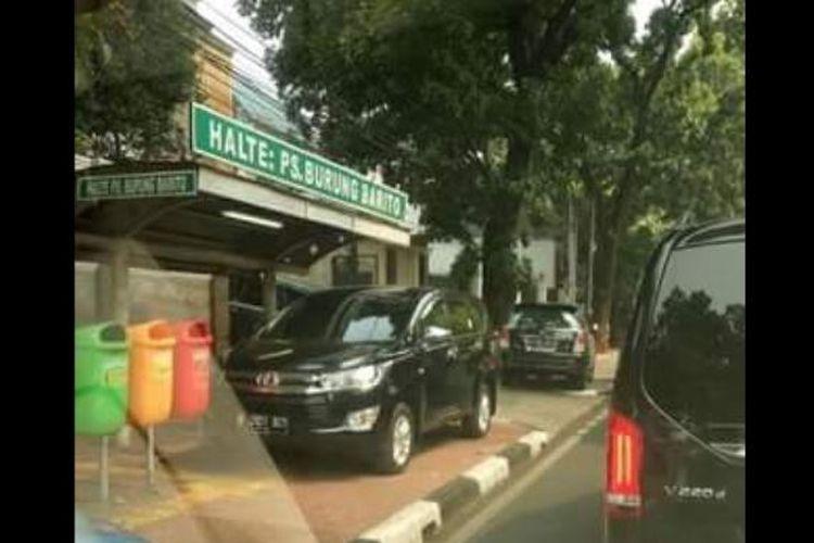 Dua mobil yang tertangkap kamera warga terparkir di trotoar jalan depan halte bus Pasar Burung Barito.