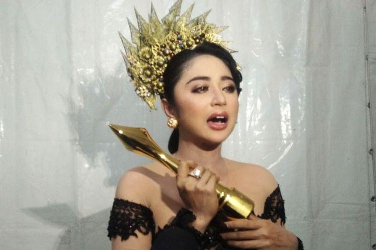 Dewi Persik memegang piala ADI 2019 kategori Penyanyi Dangdut Paling Gaya di Lapangan Galuh Mas, Karawang, Minggu (18/11/2019).