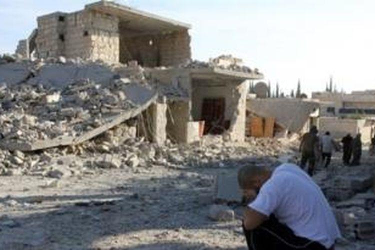 Seorang pria yang kehilangan anggota keluarganya menangis sambil duduk di depan rumahnya yang hancur akibat serangan udara pasukan rezim Suriah di desa Maaret al-Numan, Provinsi Idlib.