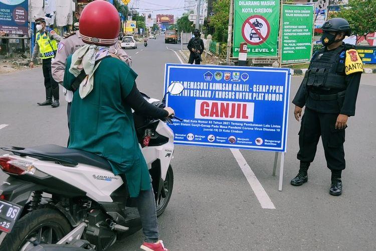 Petugas memberhentikan seorang pengendara sepeda motor yang berplat genap, saat uji coba ganjil - genap di Jalan Tuparev, Cirebon Jumat (13/8/2021). Petugas meminta pengendara putar arah dan tidak boleh masuk ke Kota Cirebon.