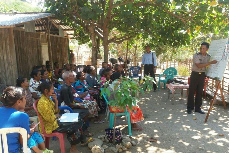 Brigpol Krispianus Ola Komek (Kresna Ola), sedang mengajari membaca dan menulis terhadap puluhan warga Dusun Weain, Desa Kenebibi, Kecamatan Kakuluk Mesak, Kabupaten Belu, Nusa Tenggara Timur (NTT) yang masih buta huruf, Sabtu (22/7/2017) di bawah pohon Waru