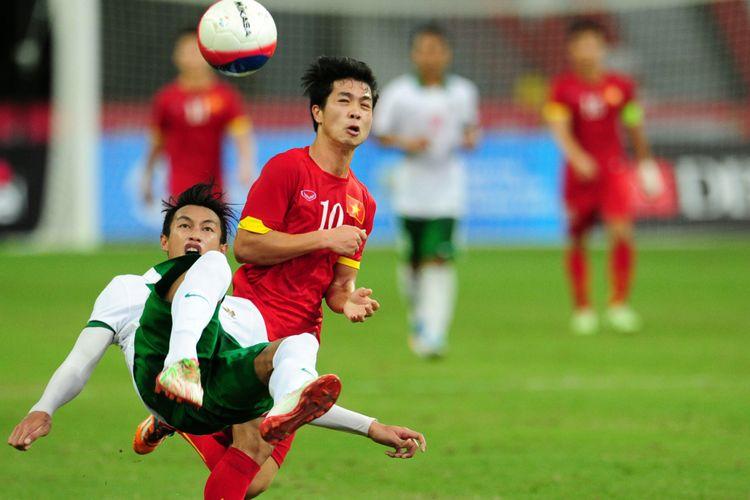 Bek Timnas Indonesia, Hansamu Yama Pranata (kiri), menyelamatkan bola dari ancaman penyerang timnas Vietnam, Nguyen Cong Phuong dalam pertandingan perebutan medali perunggu SEA Games 2015 di Singapura, 15 Juni 2015.