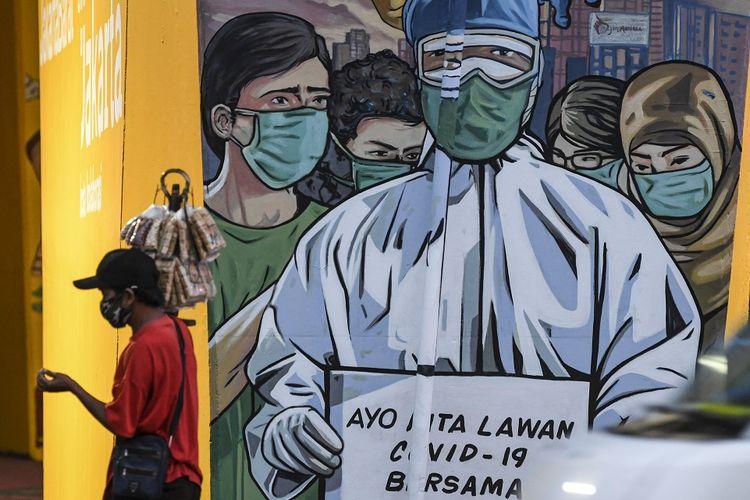Seorang pedagang yang mengenakan masker melintas di depan mural imbauan untuk melawan COVID-19 di Jakarta, Minggu (29/11/2020). ANTARA FOTO/M Risyal Hidayat/aww.