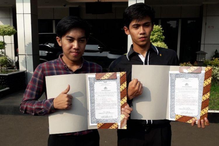 Ahmad Rafiki dan Mohamad Irfan Bahri berpose dengan piagam penghargaan yang diterimanya di Lapangan Mapolres Metro Bekasi Kota, Bekasi, Kamis (31/5/2018).