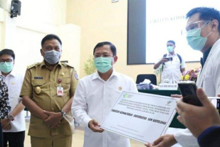 Menteri Kesehatan RI Terawan Agus Putranto didampingi Gubernur Sulawesi Utara Olly Dondokambey menyerahkan secara simbolis insentif kepada dokter residen yang membantu serta terlibat langsung dalam penanganan Covid-19 di Kampus Universitas Sam Ratulangi Manado, Selasa (25/8/2020).