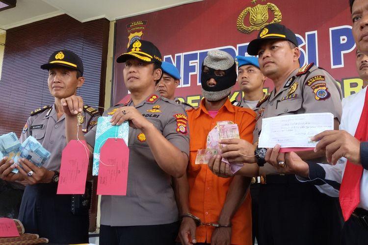 Kapolres Kulon Progo AKBP Tartono dan jajarannya menunjukkan barang bukti kejahatan Sarjimin (47), asal Bantul, tersangka penipuan dengan modus penggandaan uang.