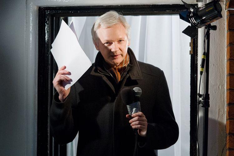Dalam foto yang diambil pada Desember 2012 ini, Julian Assange menyapa para jurnalis dari jendela kamarnya di kantor kedutaan besar Ekuador di London.