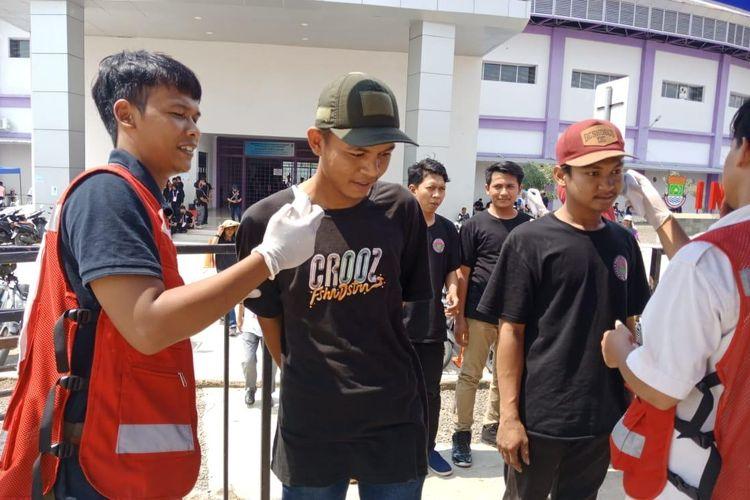 Petugas melakukan pindaian temperatur tubuh kepada para penonton yang hendak menyaksikan laga Shopee Liga 1 2020, Persita Tangerang vs PSM Makassar, di Stadion Kelapa Dua Sport Center, Tangerang, Jumat (6/3/2020). Hal ini dilakukan demi kewaspadaan di tengah wabah virus corona.