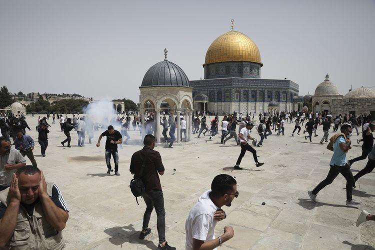Warga Palestina berlarian ketika mendengar suara ledakan dari senjata yang ditembakkan polisi Israel di Kubah Batu dalam kompleks Masjid Al-Aqsa di Yerusalem, pada Jumat (21/5/2021). Bentrokan ini terjadi tak lama setelah Israel dan Hamas menyepakati gencatan senjata usai bertempur selama 11 hari.