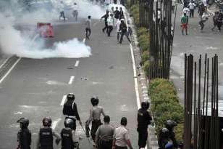 Massa demonstran berlarian menghindari tembakan gas air mata saat terjadi bentrokan dengan polisi di depan kantor KPK, Jakarta, Jumat (20/5/2016). Bentrokan terjadi saat massa dari Aliansi Masyarakat Jakarta Utara mendesak masuk ke gedung KPK untuk mendesak pemeriksaan terhadap Gubernur DKI Jakarta Basuki Tjahaja Purnama (Ahok).