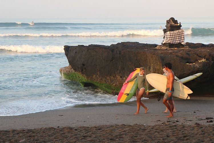 Para peselancar siang untuk berselancar di pagi hari di Pantai batu Bolong, Canggu