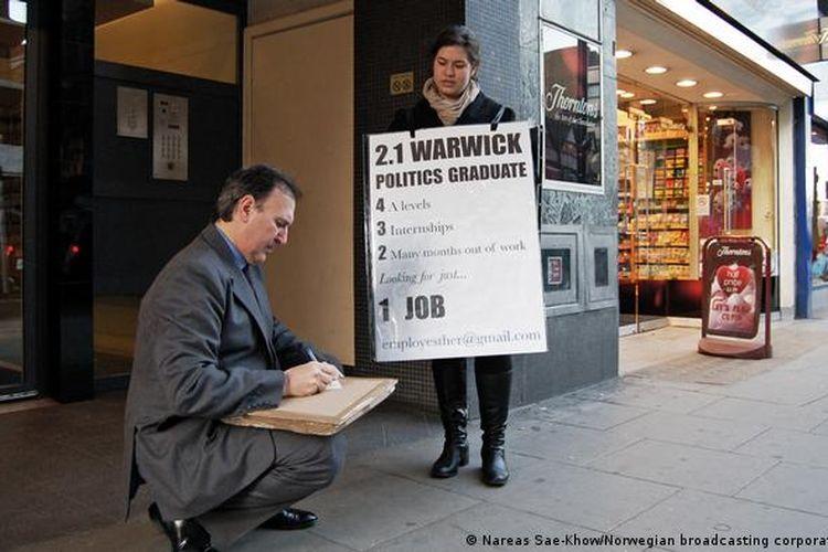 Esther Jardim yang berasal dari London, Inggris, mencari pekerjaan dengan papan yang terikat di dadanya.