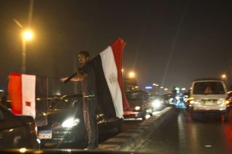 Seorang pedagang kaki lima di Kairo menjual bendera Mesir ketika para penentang Muhammad Mursi merayakan tergulingnya presiden pertama negara itu yang dipilih secara demokratis, Rabu (3/7/2013).