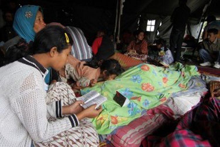 Seorang pengungsi membaca ayat-ayat Al Quran untuk mendoakan kerabat mereka yang meninggal akibat gempa ang melanda Aceh, Selasa (2/7/2013).