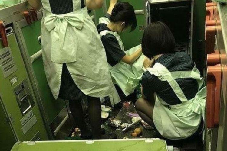 Para pramugari maskapai penerbangan Eva Air membersihkan makanan yang berhamburan akibat pesawat jurusan Taipei-Chicago itu diguncang turbulensi.