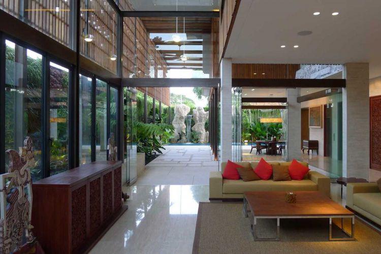 Ruang tamu di Rumah Tinggal Sanur Bali menghadap foyer yang memberi pencahayaan dan sirkulasi udara alami.
