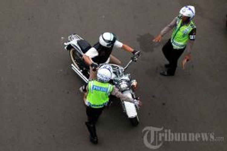 Aparat kepolisian menghentikan pengendara sepeda motor Harley Davidson B 6168 ESG yang melintas di Jalan MH Thamrin, Jakarta Pusat, Minggu (18/1/2015). Polisi menerapkan sanksi tilang bagi pengendara motor yang melintasi kawasan terlarang sepeda motor, yakni dari Jalan MH Thamrin sampai dengan Jalan Medan Merdeka Barat, mulai 18 Januari 2015.