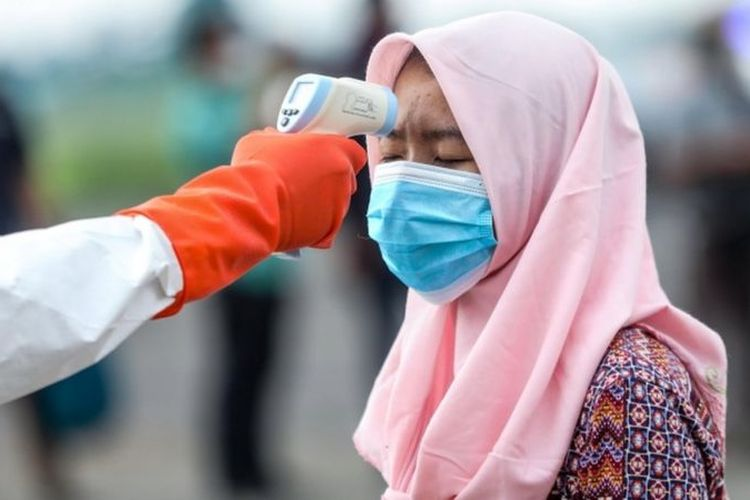 Seorang pekerja migran Indonesia diperiksa suhu tubuhnya saat tiba di Lanud Soewondo di Medan, Sumatera Utara, 10 April 2020 lalu.