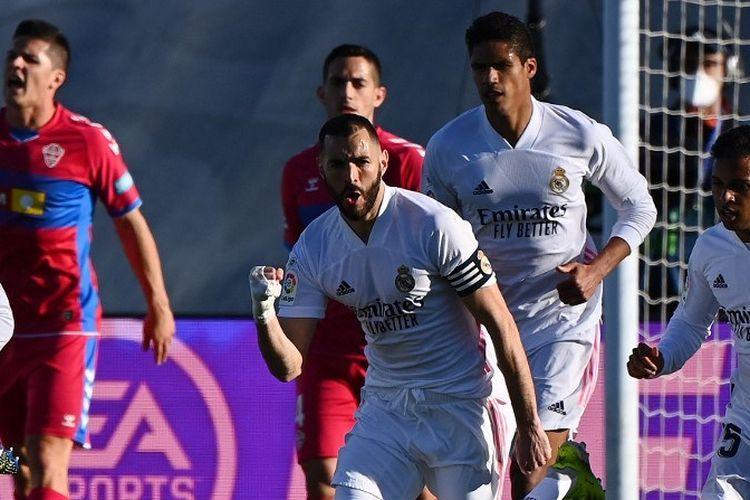 Penyerang Prancis Real Madrid Karim Benzema (tengah) merayakan bersama rekan satu timnya setelah mencetak gol dalam pertandingan sepak bola Liga Spanyol antara Real Madrid dan Elche di stadion Alfredo Di Stefano di Valdebebas, timur laut Madrid, pada 13 Maret 2021.