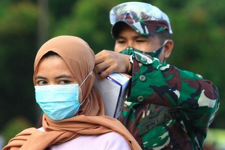 Seorang personel TNI AD memasangkan masker kepada warga yang terjaring razia kepatuhan penggunaan masker di Taman Digulis, Pontianak, Kalimantan Barat, Minggu (12/07).