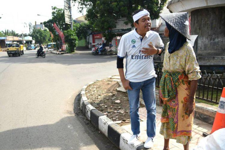 Bupati Purwakarta Dedi Mulyadi sedang berbincang mendengar curhatan sang nenek renta berumur 87 tahun asal daerahnya di pinggir jalan, Minggu (23/4/2017).