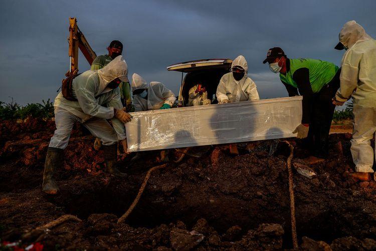 Petugas membawa jenazah untuk dimakamkan dengan protokol Covid-19 di TPU Rorotan, Jakarta Utara, Senin (28/6/2021). Tiga hektar lahan di TPU Rorotan disiapkan untuk pemakaman jenazah protokol Covid-19. Lahan seluas itu bisa menampung sekitar 7.200 petak makam.