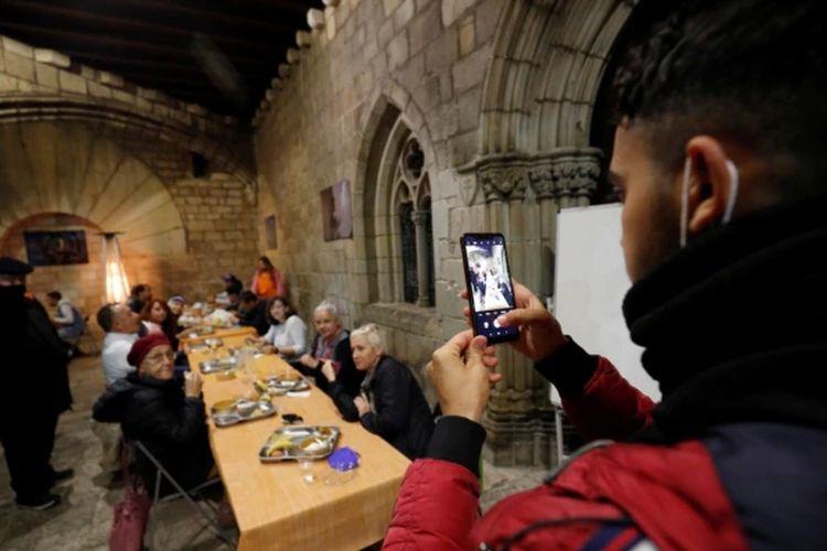 Seorang pria memotret dengan ponsel, saat iftar Ramadan di gereja Santa Anna, Barcelona, Spanyol, di tengah pandemi Covid-19, 28 April 2021.