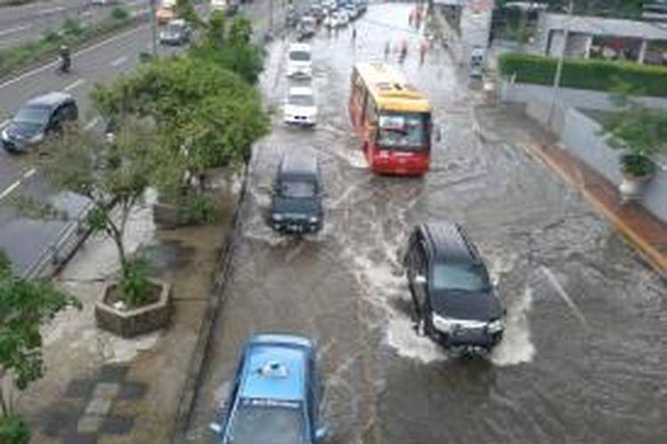 Sebuah bus Transjakarta yang harus melewati jalur reguler karena jalurnya dilewati kendaraan pribadi, imbas banjir yang menggenangi ruas Jalan S Parman, tepatnya di depan Universitas Tarumanagara, Jakarta Barat, Selasa (4/2/2014)
