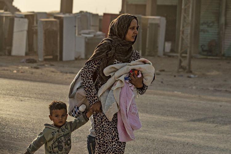 Seorang wanita membawa anak-anaknya menyelamatkan diri dari serangan bombardir oleh pasukan Turki yang menghancurkan kota Ras al-Ain di provinsi Hasakeh, yang berbatasan dengan Turki, Rabu (9/10/2019).