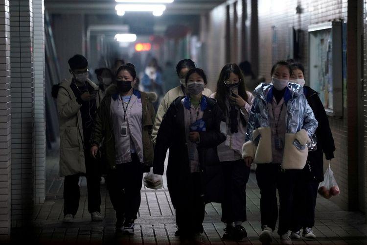 Para pekerja di China memakai masker saat keluar dari kediaman mereka di Shanghai (12/2/2020).