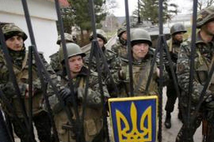 Tentara Ukraina berjaga di dalam gerbang markas mereka di Privolnoye