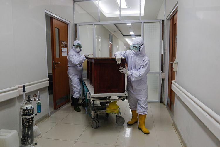 Petugas membawa keluar jenazah pasien dalam pengawasan (PDP) Covid-19 yang meninggal dari ruang isolasi RSUD Kota Bogor, Senin (11/5/2020). Mengutip laman covid19.kotabogor.go.id, tercatat Senin ini terdapat 246 PDP di Bogor, dengan 110 telah dinyatakan sembuh, 89 dalam perawatan RS, dan 47 meninggal dunia.
