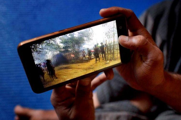 Salah satu pengungsi Rohingya di kamp Bangladesh melihat rekaman tentang kampung halamannya melalui telepon genggam.