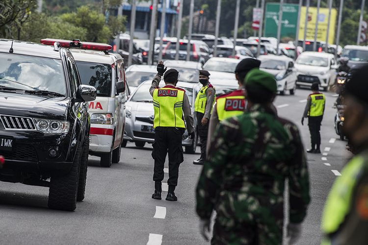 Petugas gabungan mengatur lalu lintas kendaraan dari luar kota saat penerapan pembatasan sosial berskala besar (PSBB) di Pasteur, Bandung, Jawa Barat, Rabu (22/4/2020). Pemeriksaan tersebut dilakukan untuk mengingatkan masyarakat agar menerapkan PSBB selama 14 hari dalam rangka percepatan penanganan Covid-19.