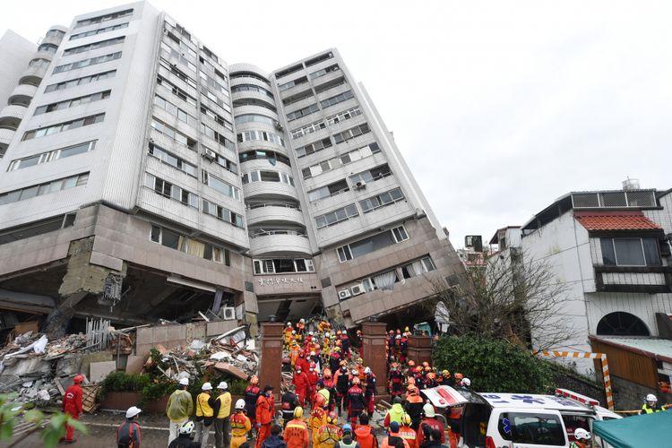 Tim penyelamat berupaya untuk mengevakuasi korban selamat sebanyak-banyaknya di dalam blok apartemen yang miring akibat gempa di Hualien, Taiwan. (AFP/Anthony Wallace)