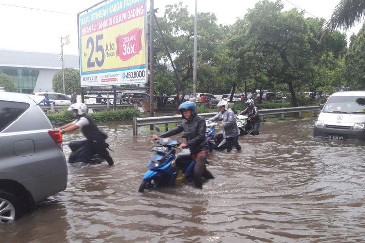 Pengendara motor menuntun sepeda motornya yang mogok akibat nekat melintasi Jalan Danau Sunter Utara yang terendam banjir, Selasa (27/3/2018).