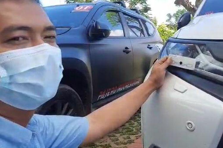 Tangkapan layar video yang memperlihatkan proses pemasangan stiker berbasis Radio Frequency Identification (RFID) di headlamp (lampu bagian depan kendaraan).